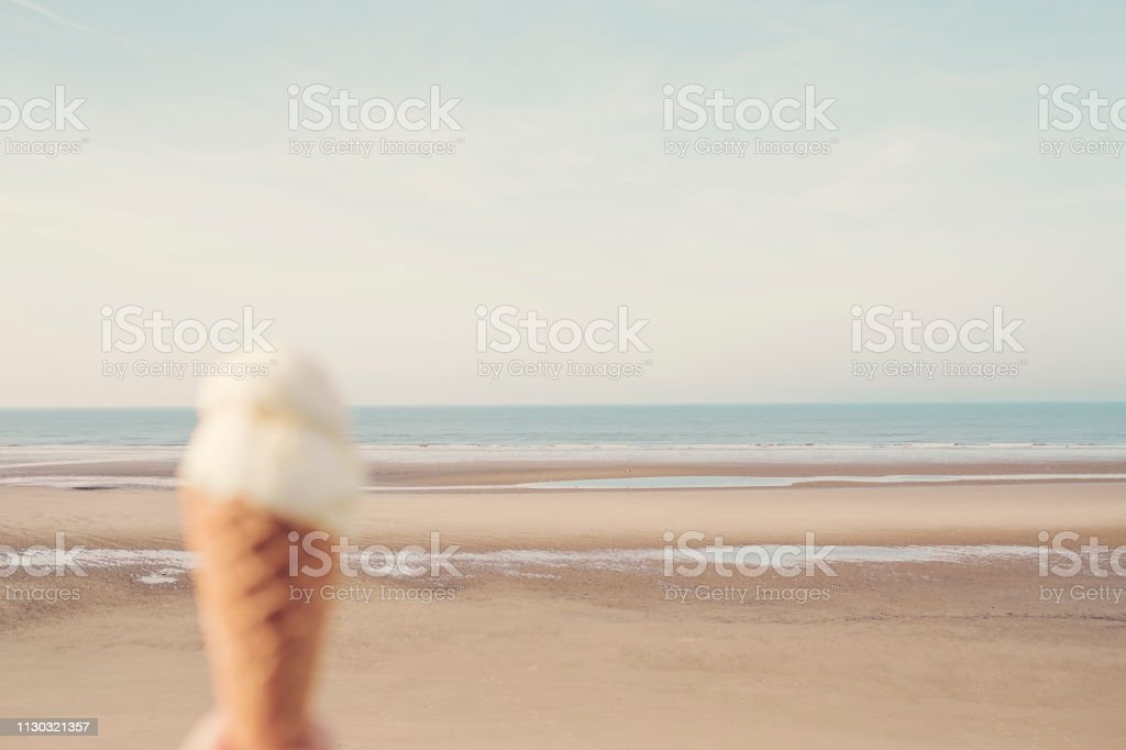 De-focused Ice Cream cone at the beach, Blackpool, low tide on a sunny day. stock photo