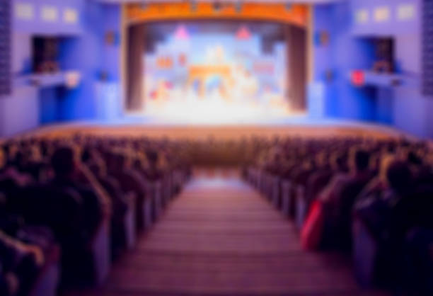 Defocused image. Auditorium in the theater during the performance. The scenery on the stage. Adults and children