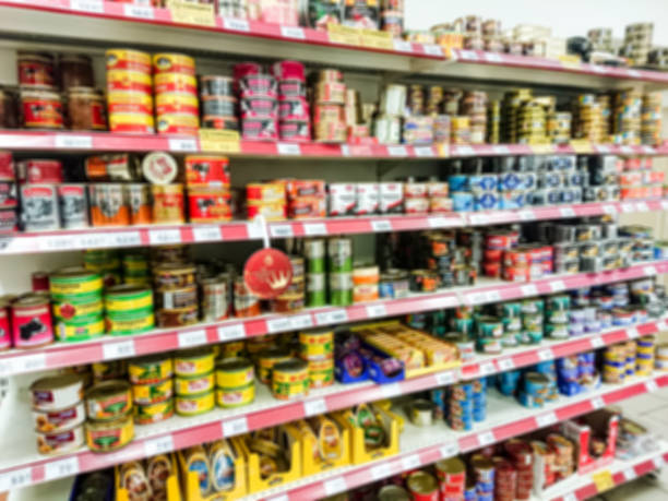 Defocused image. Canned meat and fish on the shelves in the grocery supermarket