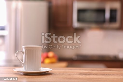 Defocused modern kitchen with coffee cup on empty wooden table or countertop in foreground.  Stainless steel appliances  No people.