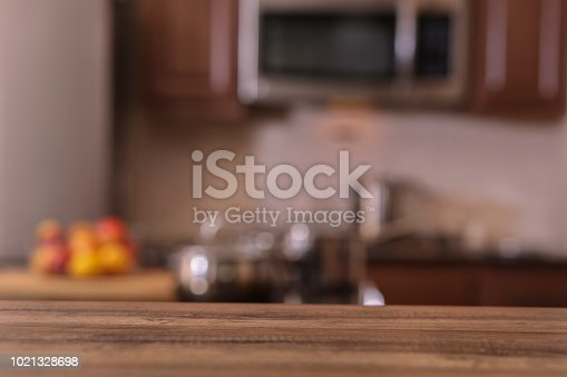 Defocused modern kitchen with empty wooden table or countertop in foreground for object placement.  Stainless steel appliances and cooking pots and a bowl of fruit in background.   No people.