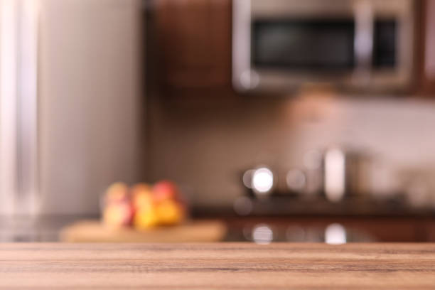 Defocused kitchen with empty wooden table foreground. stock photo