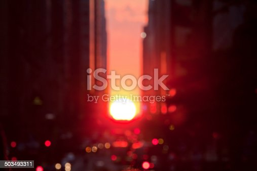 Defocused photo of Manhattanhenge.  Can be Used for background.  Manhattanhenge is a circumstance which occurs twice a year, during which the setting sun aligns with the east–west streets of the main street grid in the borough of Manhattan in New York City.