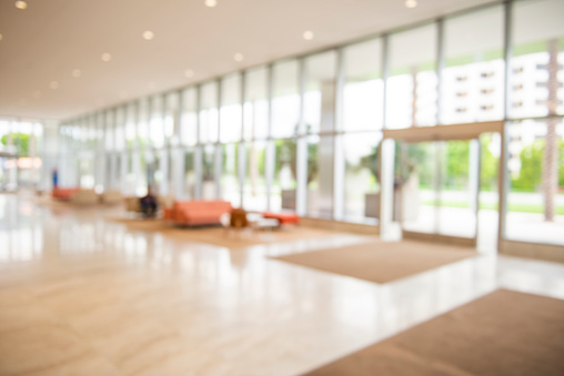 Out of focus modern corporate lobby with seating area nd windows.