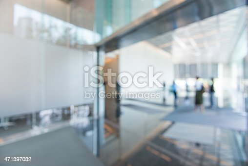 Out of focus office building lobby area background. The public space has business people arriving to work