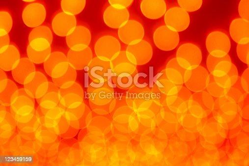 123458999 istock photo defocused orange light dots against red background 123459159
