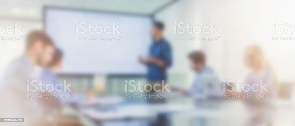 Defocused panoramic photo of man presenting his work stock photo