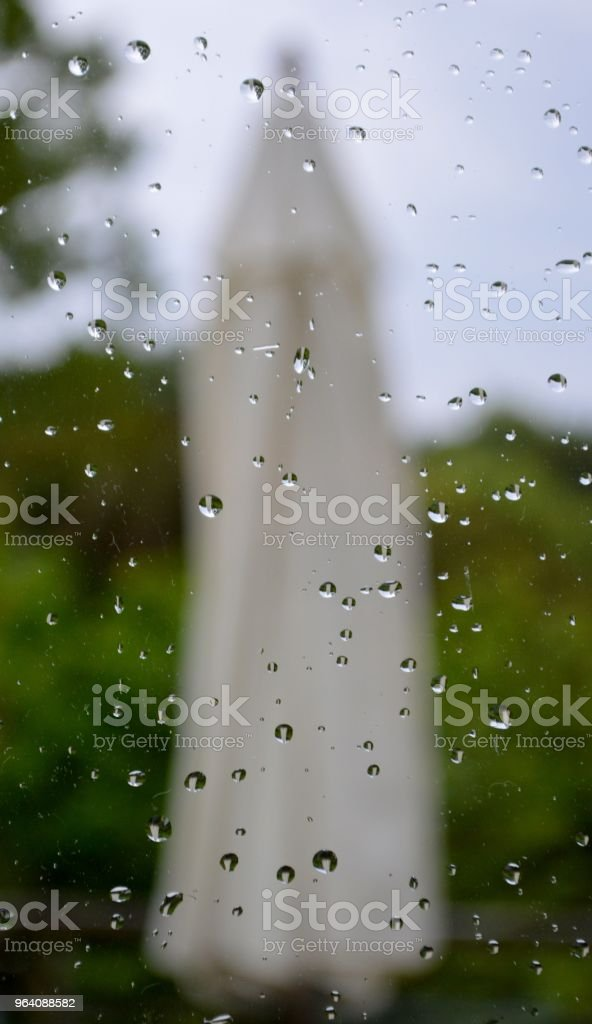 A defocused parasol seen through a window on a rainy day - Royalty-free Close-up Stock Photo