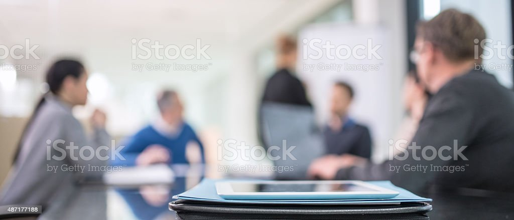 Defocused people at business meeting Panoramic shot of business team at the meeting working on project. 2015 Stock Photo