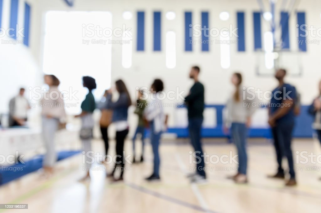 Defocused photo multi-ethnic group lined upto vote A defocused photo of a diverse gorup of people standing in line to sign up to vote. Adult Stock Photo