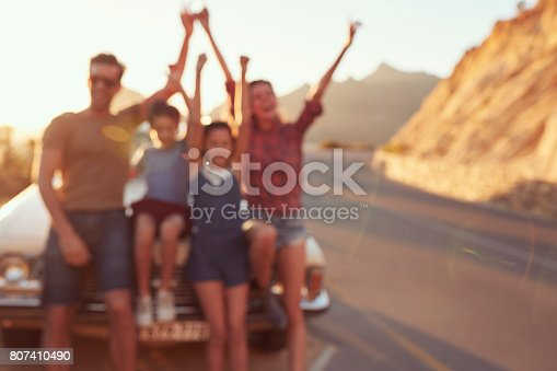 807410158 istock photo Defocused Portrait Of Family Standing Next To Classic Car 807410490