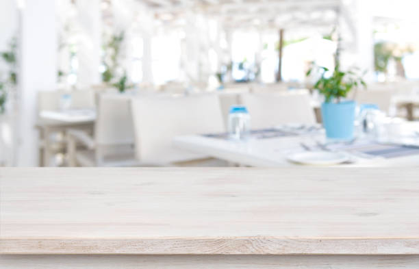 Defocused resort restaurant background with wooden table top in front stock photo