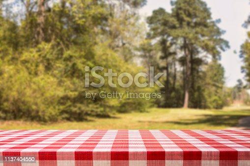 1048926386istockphoto Defocused summer park scene with blank picnic table. 1137404550