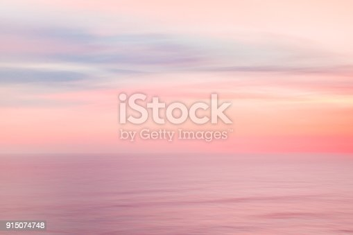 Defocused sunrise sky and ocean nature background with blurred panning motion.