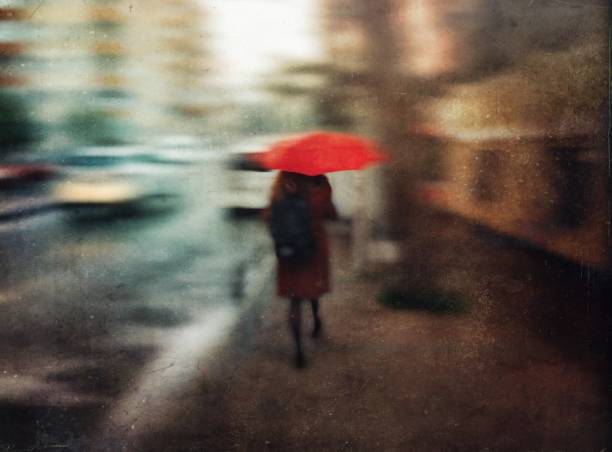 Defocused textured view of a woman with red umbrella walking on the street