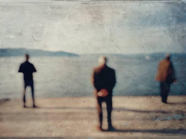 Defocused textured view of three men on the coastline