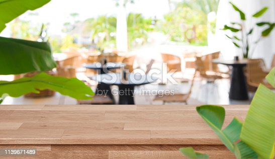 istock Defocused tropical summer cafe background in front of wooden tabletop 1139671489