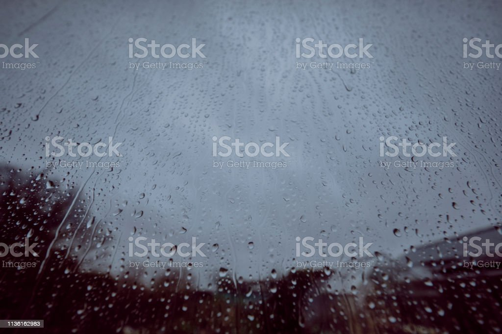 defocused view through a window covered in rain on a grim overcast rainy day. stock photo