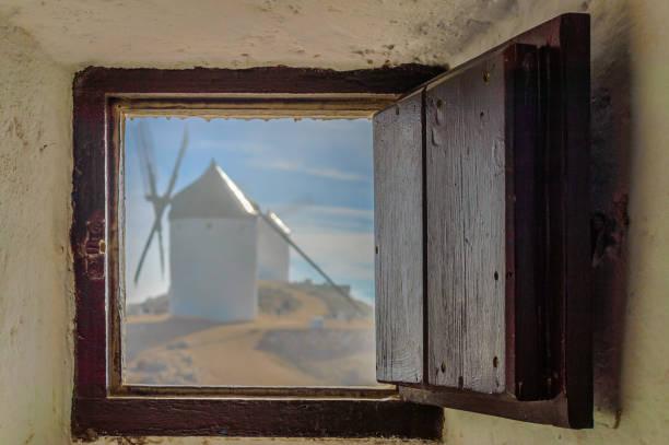 Defokussierte Windmühle durch ein Fenster einer anderen Mühle mit Nebel in consuegra gesehen ... 26. Dezember 2018. Consuegra Toledo Castilla La Mancha Spanien Europa. – Foto