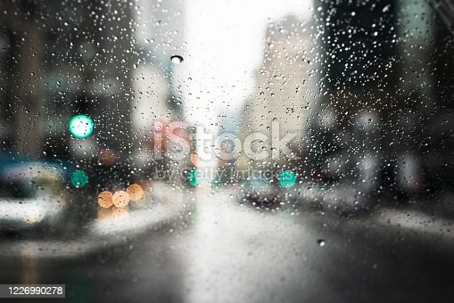 Close-up of raindrops on a car's windshield, with the city defocused in the background.
