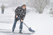 Defocused young man, male in winter coat cleaning, shoveling driveway, street from snow in heavy snowing snowstorm, holding shovel, residential houses, snowflakes falling