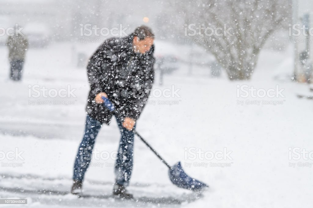 Defocused young man, male in winter coat cleaning, shoveling driveway, street from snow in heavy snowing snowstorm, holding shovel, residential houses, snowflakes falling stock photo