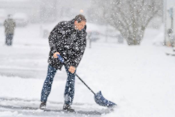 intreepupil jonge man, mannelijke in winter jas schoonmaken, gekwetsten oprit, straat van sneeuw in zware sneeuwstorm sneeuwt, vasthouden schop, residentiële huizen, sneeuwvlokken vallen - graven stockfoto's en -beelden