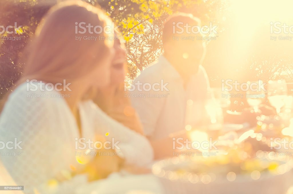 Defocussed group of young people eating outdoors. stock photo