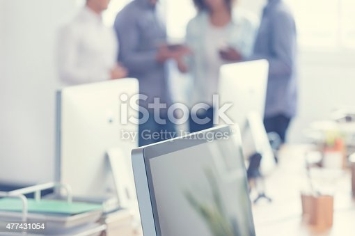 istock Defocussed image of 4 people working on a digital tablet. 477431054