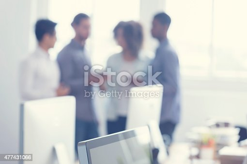 istock Defocussed image of 4 people working on a digital tablet. 477431066