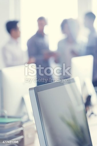 istock Defocussed image of 4 people working on a digital tablet. 477431098