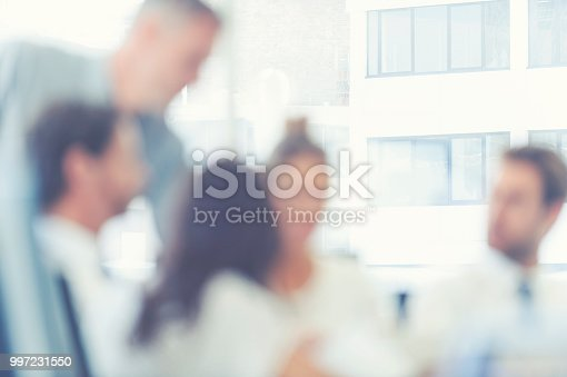 istock Defocussed image of a group of business people meeting. 997231550