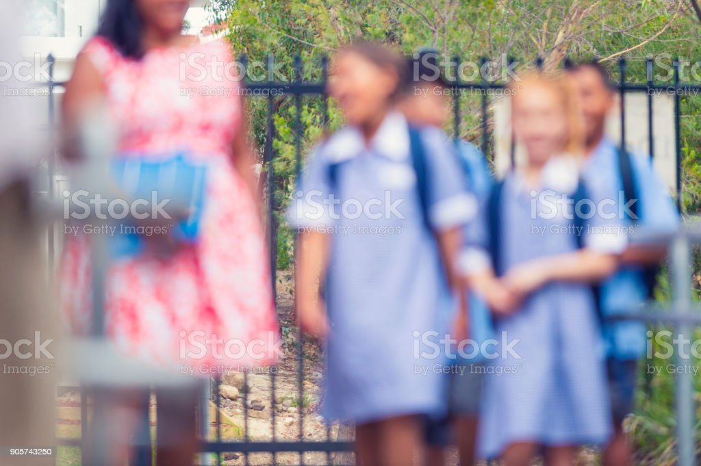 Defocussed shot of children and teacher walking. stock photo