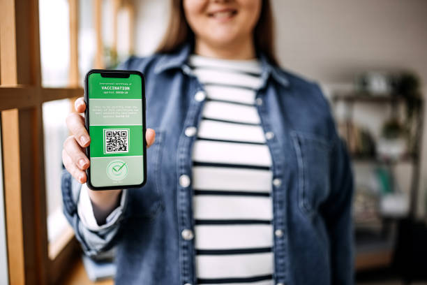Defocussed young woman holding smartphone with certificate of vaccination against the Covid-19 stock photo