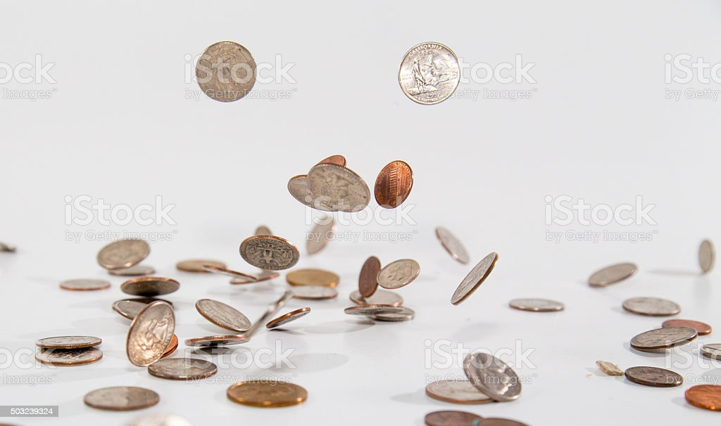 Defying Gravity - Loose change hitting the table stock photo