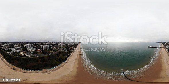 360 Degree Full Sphere Panoramic Photo of the wonderful Bournemouth Beach in the UK, showing the coatal beach and the famous Bournemouth pier on a cloudy day.