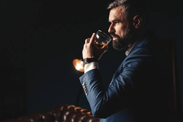Degustation, Verkostung. Mann mit Bart hält Glas Schnaps. Verkostungs- und Degustationskonzept. Bärtiger Geschäftsmann im eleganten Anzug mit Glas Whiskey – Foto