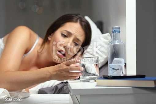 Dehydrated woman reaching a glass of water on the bed in the night at home