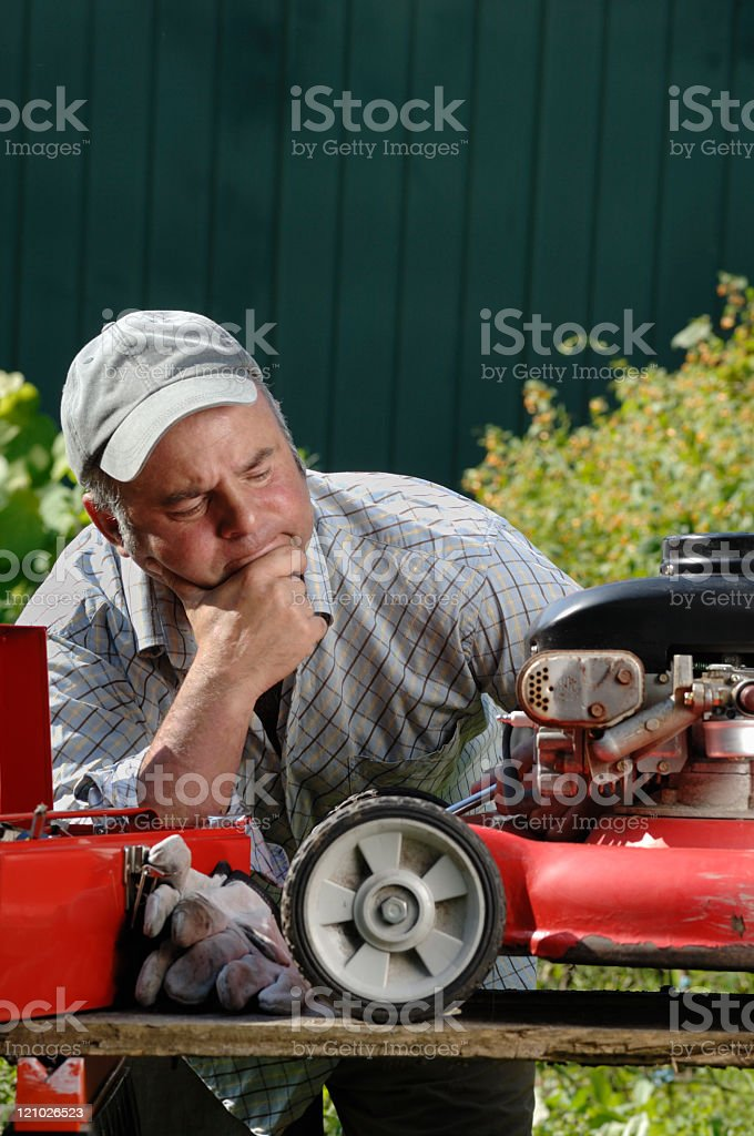 Dejected man trying to fix a broken lawnmower stock photo