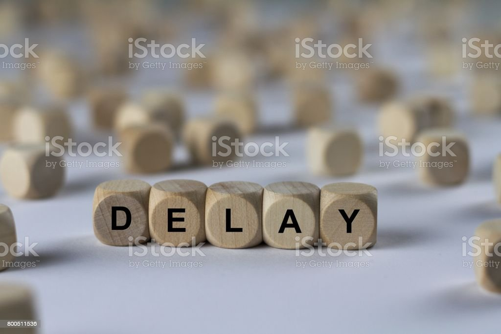 delay - cube with letters, sign with wooden cubes stock photo