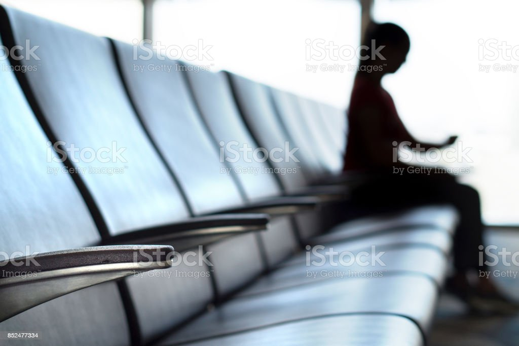 Delayed and cancelled flight concept. Silhouette woman looking her watch in airport terminal to see the time in airport waiting room and departure lounge. stock photo