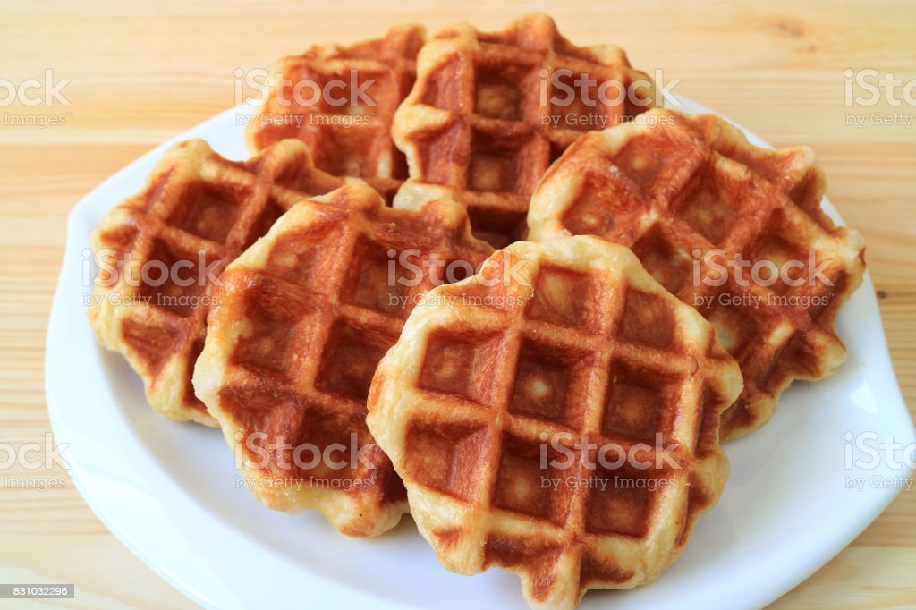 Delectable Belgian Waffles on White Plate Served on Wooden Table stock photo