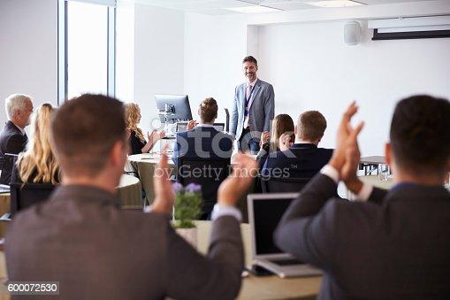 600073884 istock photo Delegates Applauding Businessman Making Presentation 600072530