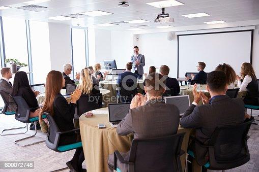 600073884 istock photo Delegates Applauding Businessman Making Presentation 600072748