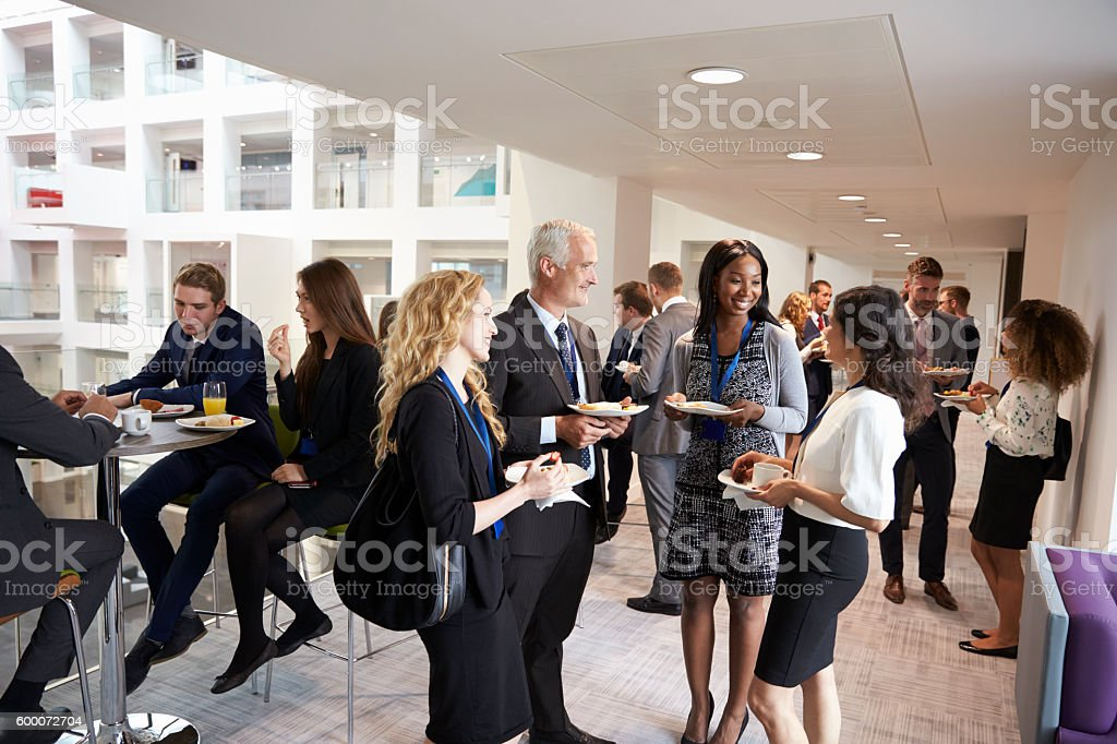 Delegates Networking During Conference Lunch Break - foto de stock