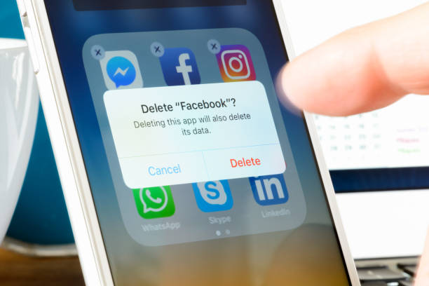 deleting facebook app from smartphone - delete key stock photos and pictures