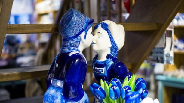 Delft blue sculpture of young kissing couple in a souvenir shop in Amsterdam. stock photo
