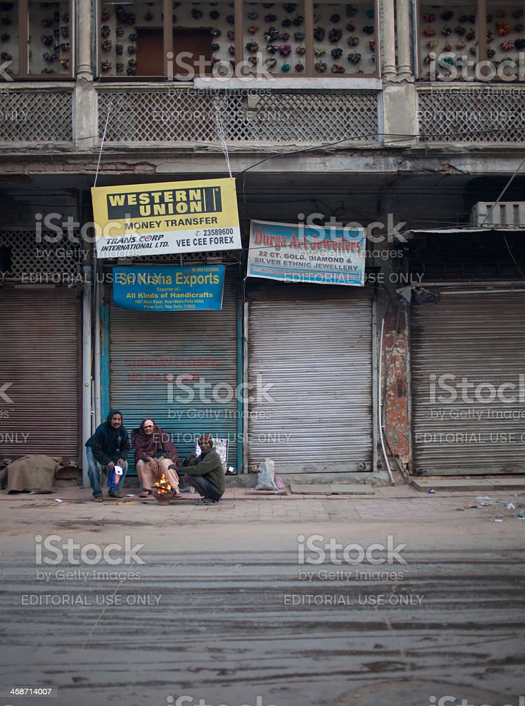 Delhi, India: Homeless people sitting near the fire royalty-free stock photo