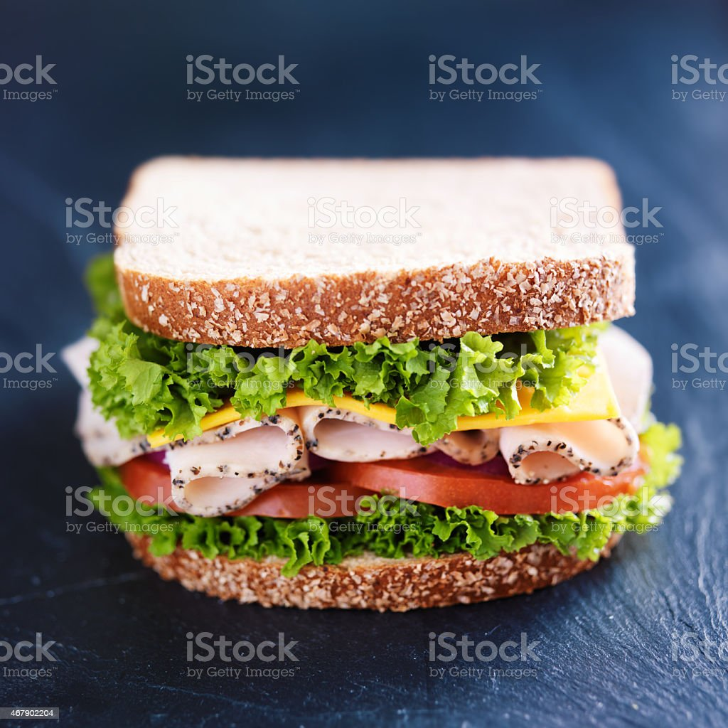 deli meat turkey sandwich on slate surface stock photo