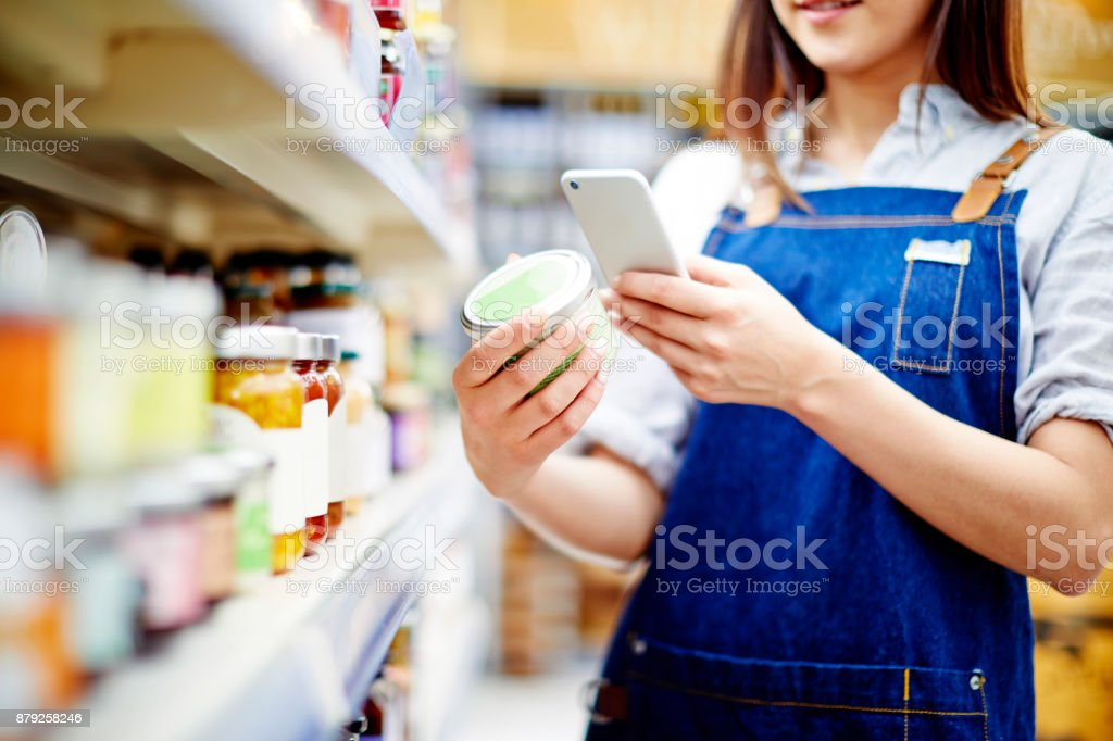 Deli owner scanning label on food container with smart phone - Royalty-free Adult Stock Photo